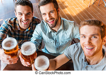 Cheers! Top view of three happy young men in casual wear toasting with beer while sitting in bar together