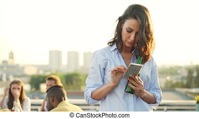 Cheerul brunette pretty girl is using smart phone touching screen standing on rooftop with beer bottle in her hand while her friends are partying in background.