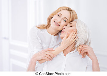 Cheerul delighted woman embracing her mother