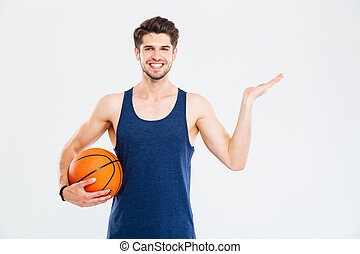 Cheerul young sportsman with basketball ball holding copyspace on palm