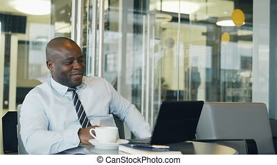 Cheery African American businessman smiling, printing and working on his laptop in glassy cafe during lunch break. He is showing yes gesture looking happy