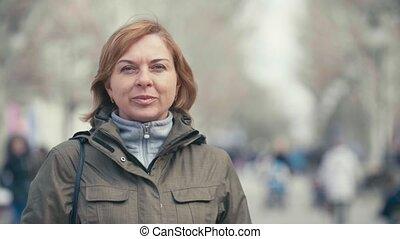 Cheery blond woman in a sportive green jacket walking in a...