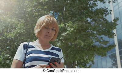 Cheery blonde woman standing and surfing the net on phone in...