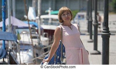 Cheery blonde woman standing in Dnipro quay and entertaining...