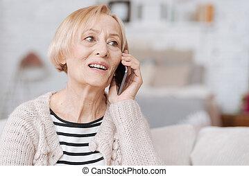 Cheery elderly woman calling her friend