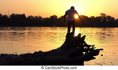 Cheery man climbs the tree roots on a lake bank in slo-mo