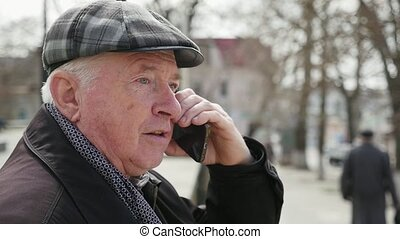 Cheery old man talks on his smartphone with his friend in...