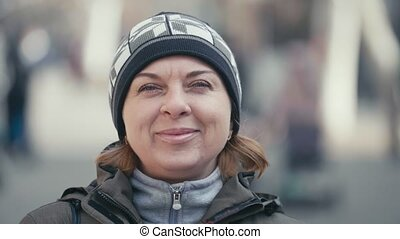 Cheery woman in a knitted hat and a sportive hoodie smiling...