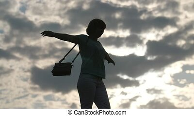 Cheery woman stretching out her hands and turning around at sunset in slo-mo