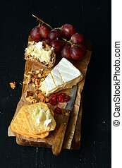 cheese and crackers on old wooden board