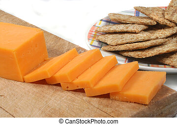 cheese and crackers - sliced cheddar cheese and wheat ...