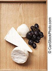 Cheese and grape on wooden background