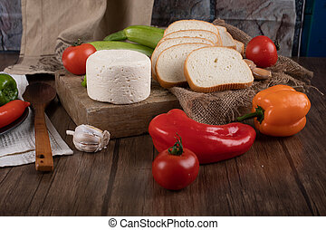 Cheese and vegetables on a wooden table