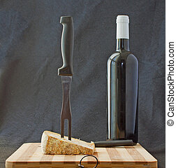 Cheese with big fork and bottle of red wine