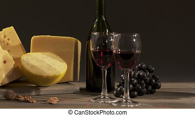 Cheese and wine on a dark background. Different types f cheese