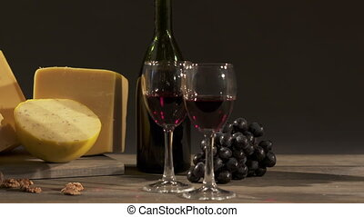 Cheese and wine on a dark background. Different types of cheese
