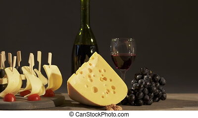 Cheese and wine tasting. Two glasses with red wine, grapes...