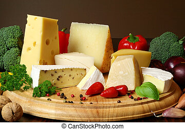 Variety of cheese and vegetables: camembert, gouda, brie with nuts, parmesan, goat, sheep and other hard cheeses