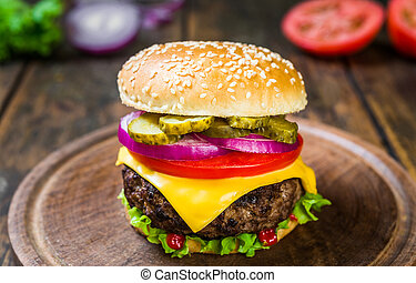 Cheese burger with cheese against wooden background. Tasty fast food.