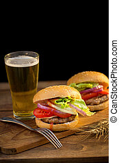 Cheese burger with grilled meat, cheese, tomato, on craft paper on wooden surface. Fast food template. with beer.