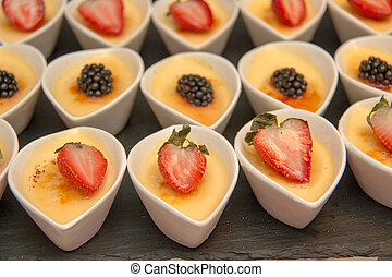 cheese cake in white cup ontop fruit - A cheese cake in...