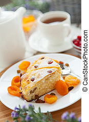 Cheese cake with tea, dried apricot and raisins closeup on a plate. Tasty dessert decorated
