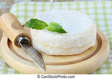 Cheese camembert on a wooden plate and  herbs