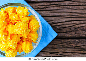 Cheese flavored popcorn in bowl on wooden table