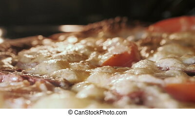 Cheese on pizza melts from oven heat. - Cheese on pizza...