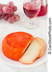 cheese on plate with glass of wine