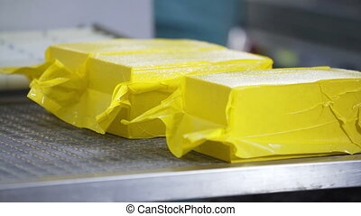 Cheese packaging process. Close up of cheese processing at...