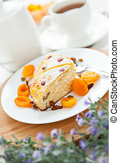 Cheese Pie with tea, dried apricot and raisins closeup on a plate