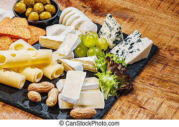 Cheese plate. Assorted different types of cheese with olives, grapes and chips on a black plate on a wooden table,assorted cheeses, nuts and grapes on a wooden table.