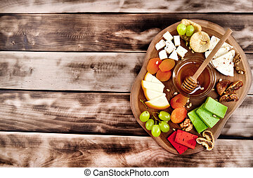 Cheese plate - various types of cheese, honey, grapes, dried apricots, nuts and figs on a wooden board on dark wooden background.