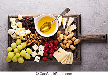 Cheese plate with nuts, honey and grapes - Cheese plate with...