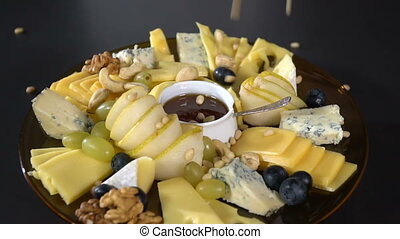 Cheese platter sprinkled with pine nuts. slow motion -...