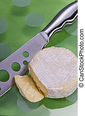 Cheese platter - A glass platter on a green table cloth with...