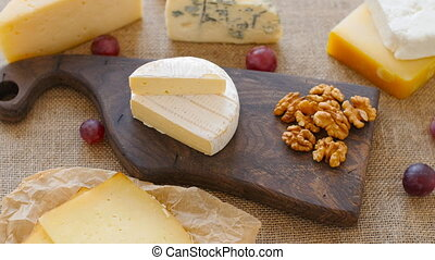 Cheese platter with nuts and grapes on a wooden cutting...