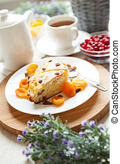 Cheese pudding with tea, dried apricot and raisins closeup