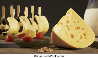 Cheese skewers appetizers and wedge of Swiss cheese on an...