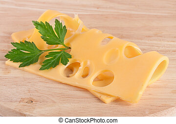 cheese slice with leaf parsley on cutting board