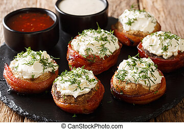 Cheese stuffed mushrooms wrapped in bacon served with sauces close-up on a plate. horizontal