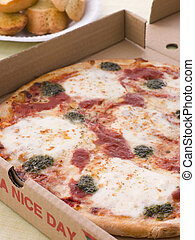 Cheese, Tomato And Pesto Pizza In A Take Away Box With...