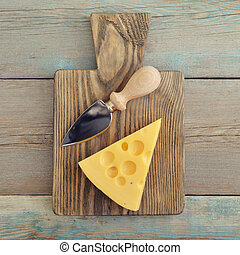 Cheese with big holes and knife on wooden cutting board