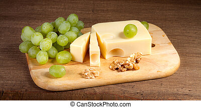 Cheese with brush of grapes and walnuts on a wooden table
