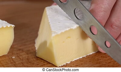 Cheese with white mold cut with a knife on a cutting board. slow motion 100fps