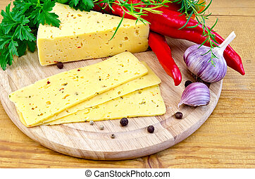Cheese with spices and herbs on a round board