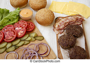 Cheeseburger ingredients on a white wooden background, side view. Close-up.