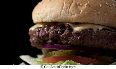 Cheeseburger on black background. Closeup of burger...