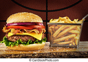 Cheeseburger with bacon and a basket of french fries. Basketball ball image in background.